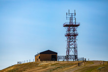 A Wide Angle View Of A Steel Lattice Cellular Base Station Tower By A Small Brick Building Atop A Hill Against A Blue Sky. 3G, 4G, 5G Mobile Coverage