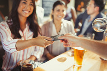 Smiling Woman Paying Bartender...