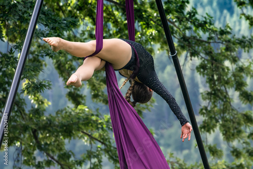 Obraz na plátně An elegant gymnast is seen suspended in a forest, using aerial silks during a flowing dance routine, body intertwined with fabric
