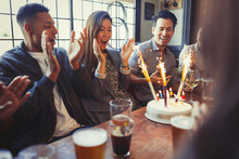 Friends Cheering For Woman Celebrating Birthday Fireworks Cake At Table In Bar