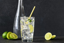 Glass Of Sparkling Water With Ice Cubes And Slice Of Lime