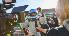 News Reporter Cameraman Interviewing Formula One Driver Cheering, Celebrating Victory