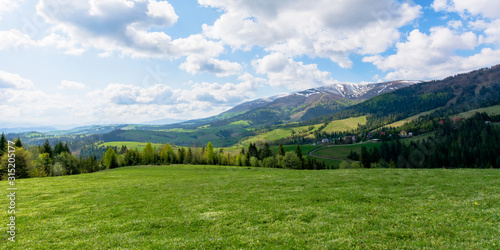 mountainous countryside landscape in spring. grassy meadow on top of a hill. mountain ridge with snow capped tops in the distance. sunny weather with clouds on the blue sky - 315205177