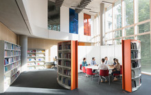 Business People Meeting At Round Table In Open Plan Library