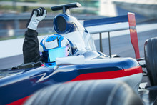 Portrait Formula One Race Car Driver Wearing Helmet Cheering Fist On Sports Track
