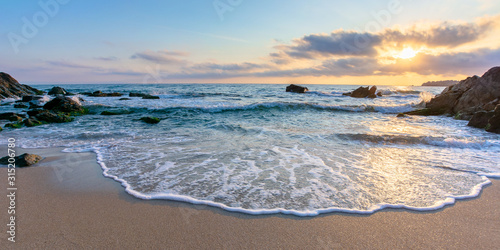 Fototapeta sunrise on the beach. beautiful summer scenery. rocks on the sand. calm waves on the water. clouds on the sky. wide panoramic view obraz