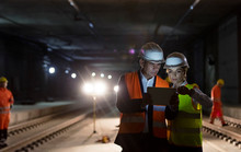 Foreman Construction Worker Using Digital Tablet At Dark Underground Construction Site