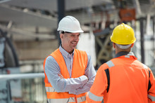 Smiling Foreman Talking To Construction Worker At Construction Site