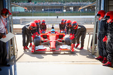 Pit Crew Pushing Formula One Race Car Into Repair Garage