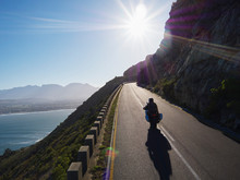 Couple Riding Motorcycle On Sunny Road Along Ocean