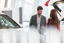 Car Salesman Helping Female Customer In Car Dealership Showroom