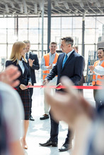 Business People Cutting Ribbon At New Construction Site Ceremony