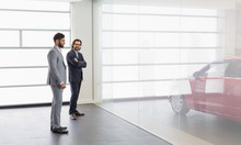 Car Salesman Male Customer Looking At New Car In Car Dealership Showroom