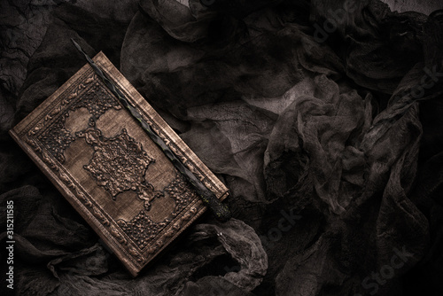 Old book with spells and magic wand on gray background with witch rag Wallpaper Mural