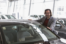 Portrait Smiling Male Customer Shopping For New Car In Car Dealership Showroom