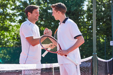 Smiling Young Male Tennis Players Handshaking In Sportsmanship Over Net On Tennis Court