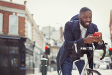 Young Businessman Commuting Bicycle, Texting Cell Phone On Sunny Urban Street