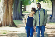 Young Couple Holding Hands, Walking In Park