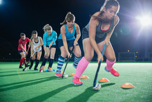 Determined Female Field Hockey Players Practicing Sports Drill On Field At Night