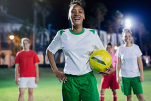 Portrait Confident, Laughing Young Female Soccer Player Practicing On Field At Night