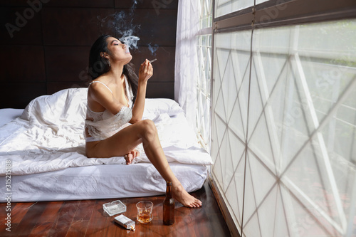 drunken asian woman in white lingerie, drinking and smoking while holding bottle Tapéta, Fotótapéta