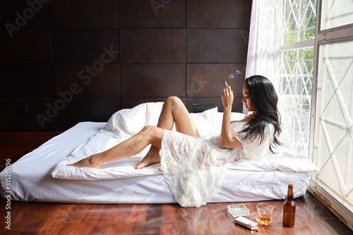 side view drunken asian woman in white lingerie, drinking and smoking while hold Tapéta, Fotótapéta