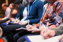 Business People Taking Notes In Conference Audience