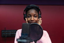 Portrait Confident Teenage Girl Musician Recording Music, Singing In Sound Booth