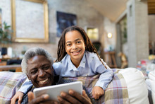 Portrait Smiling Grandfather And Granddaughter With Digital Tablet