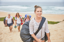 Portrait Smiling, Confident Female Paraglider Carrying Parachute Backpack On Beach
