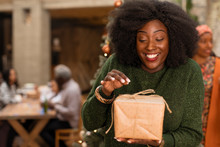 Curious, Enthusiastic Young Woman Opening Christmas Gift