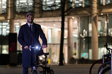 Portrait Confident Businessman With Bicycle On Urban Street At Night