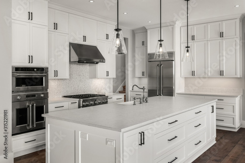 Obraz na plátně Beautiful kitchen in new luxury home with stainless steel appliances, pendant li