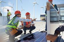 Female Engineers Talking, Examining Solar Panels At Power Plant