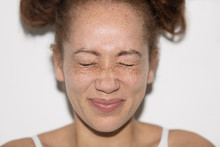 Portrait Playful Young Woman With Freckles Squeezing Eyes Shut