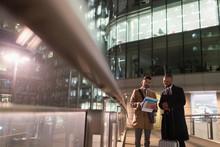 Businessmen Suitcase Discussing Paperwork On Urban Pedestrian Bridge At Night