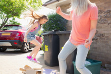 Mother Playful Daughter Breaking Down Cardboard For Recycling Outside House
