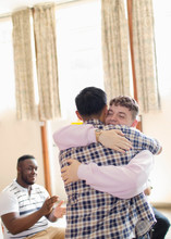 Men Hugging In Group Therapy