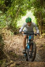 Happy Man Mountain Biking On Trail In Woods