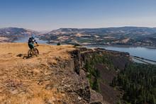 Man Mountain Biking On Cliff Along Columbia River, Hood River, Oregon, USA