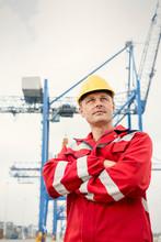 Confident Dock Worker Below Crane At Shipyard