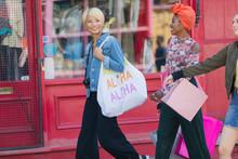 Young Women Friends Shopping On Urban Sidewalk