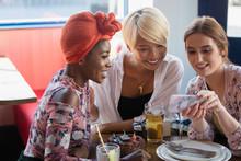 Young Women Friends Using Smar...