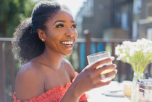 Happy Young Woman Drinking Ora...