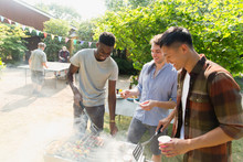 Young Men Barbecuing In Sunny Backyard