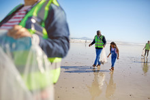 Grandfather Granddaughter Volunteers Cleaning Up Litter On Sunny Wet Sbeach