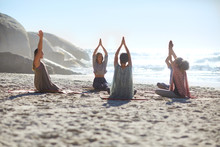 Serene People In Circle Meditating On Sunny Beach During Yoga Retreat