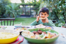 Boy Eating Naan Bread At Dinner Table