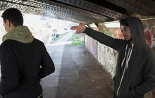 Menacing Young Man Gesturing Finger Gun At Man In Urban Tunnel