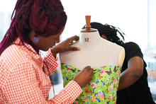 Female Fashion Designers Pinning Butterfly Fabric On Dressmakers Model